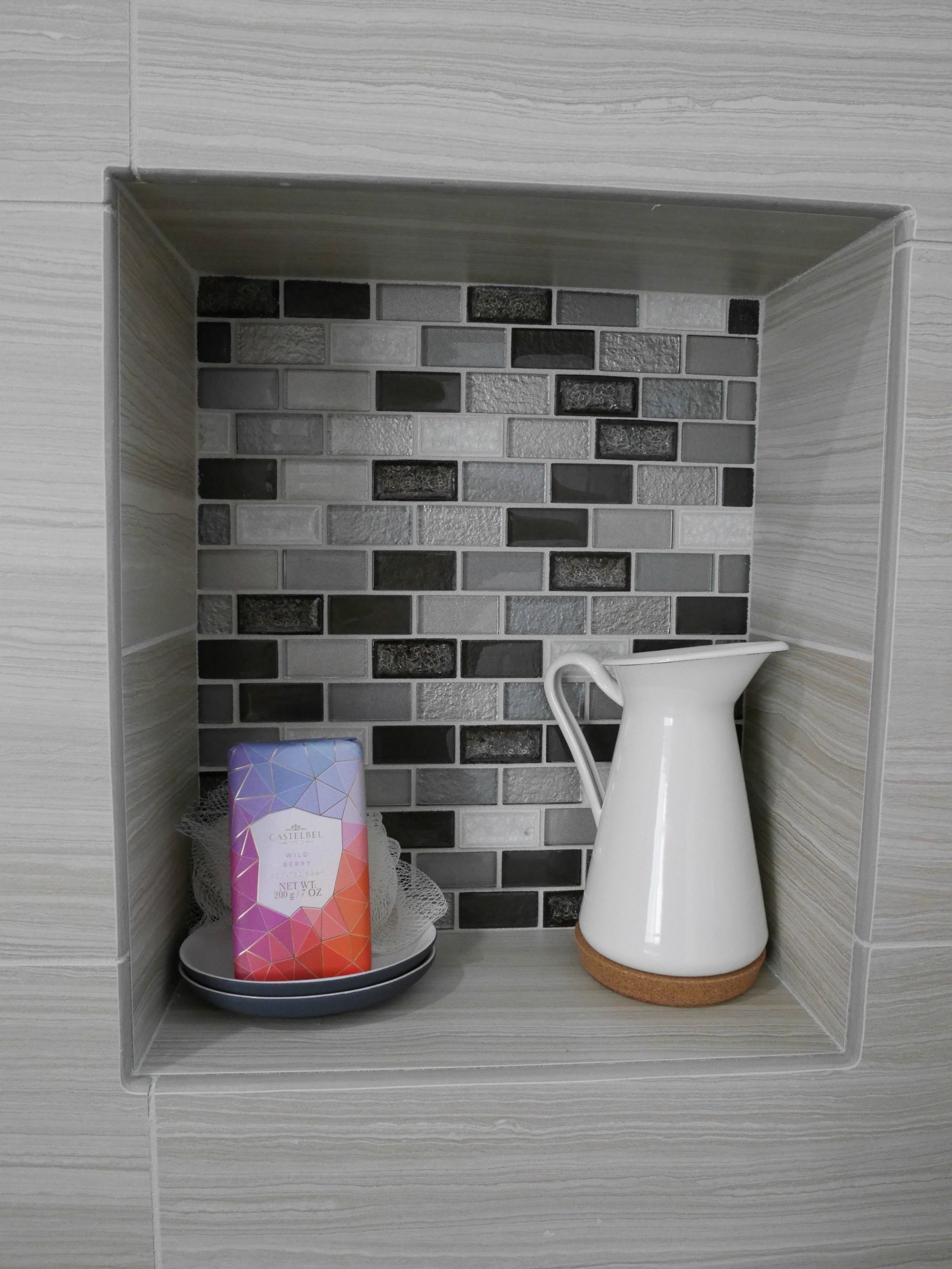 Recessed storage shelf with multi-colored grey, black and white tiles