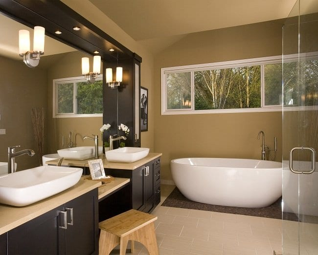 Bathroom with two vessel sinks, a freestanding tub, dark walnut vanity, and tan walls