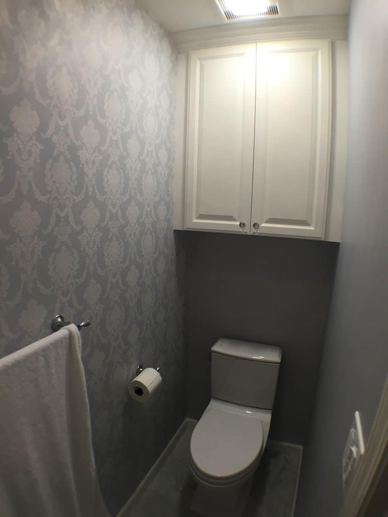Toilet room with patterned walls and a simple white cabinet