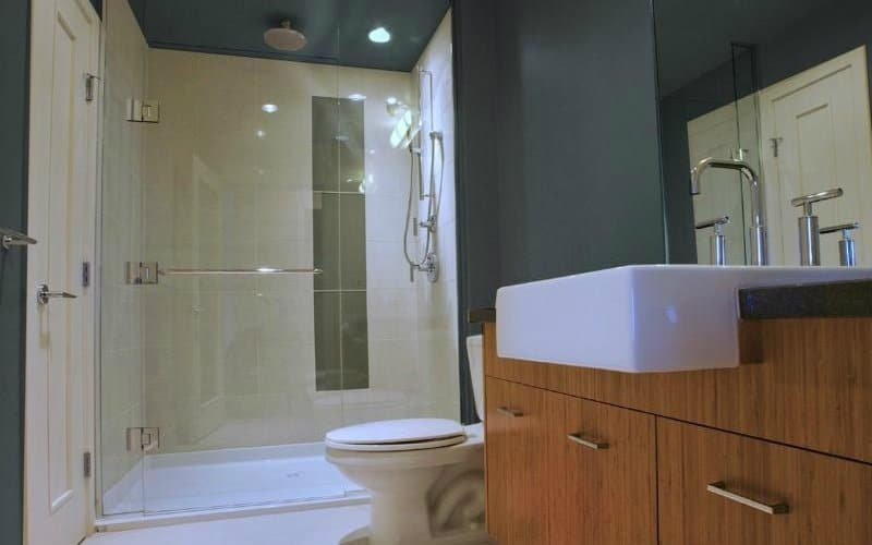 Shower with white tile walls in a bathroom that also has grey walls and a sink on a wooden vanity