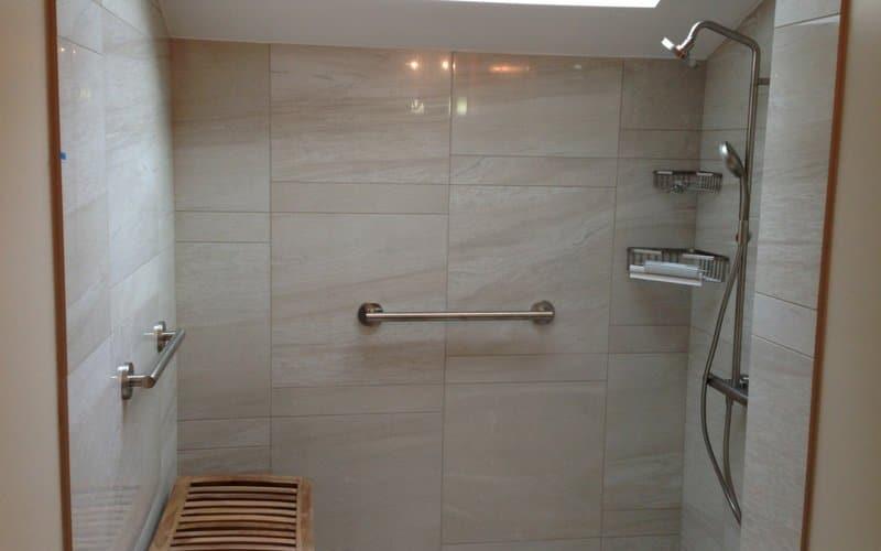 Shower with cream colored tile walls