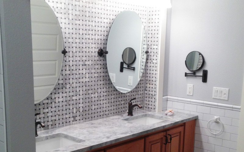 Two oval shaped mirrors mounted on a patterned bathroom wall