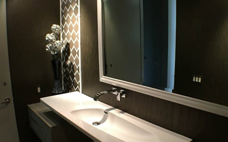 Large bathroom mirror set on a dark brown wall above a white, rectangular sink