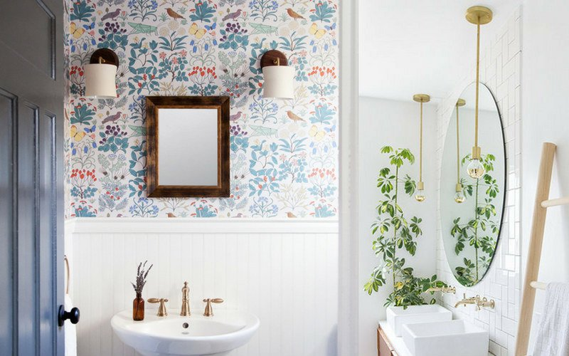 Bathroom with floral wall paper, white sink, and green plant in the corner