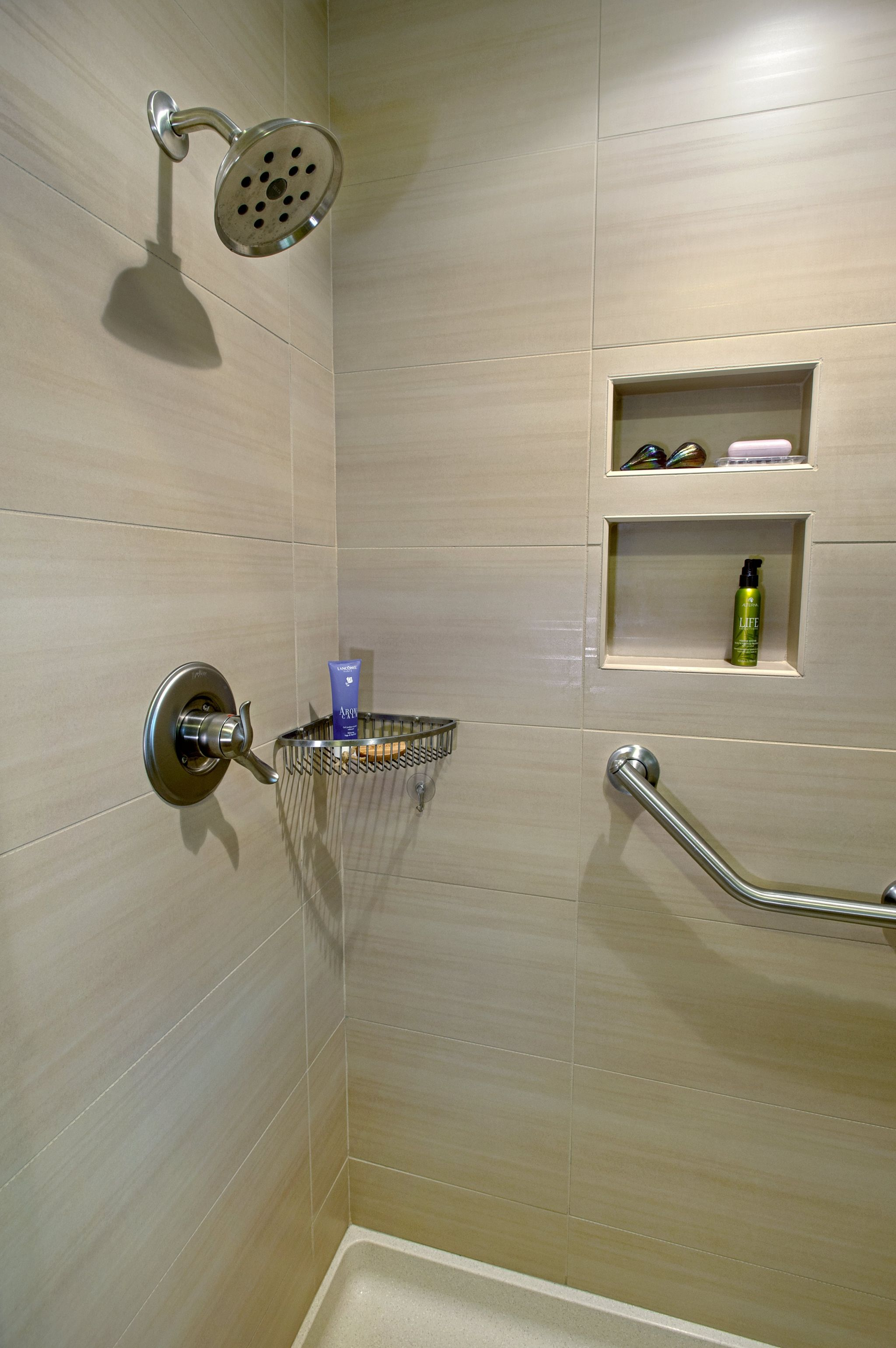 Shower with a small, silver storage basket mounted in the front right corner
