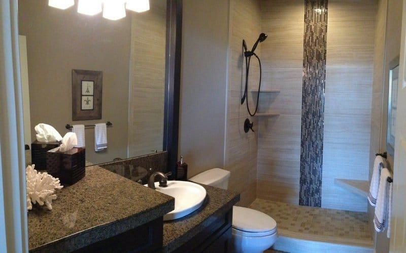 Bathroom with grey walls, an open shower, and a lowered sink