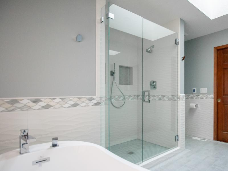 Remodeled blue and white tile shower with glass doors