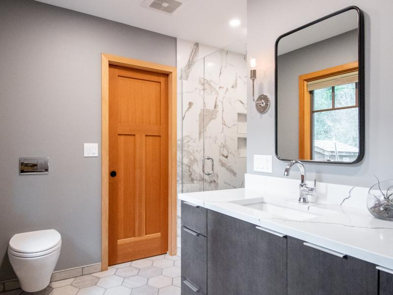 Remodeled bathroom with tile shower and wall mounted toilet
