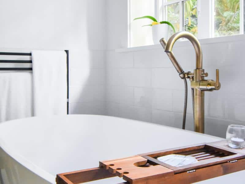 Freestanding bathtub with floor mounted tub filler and towel warmer