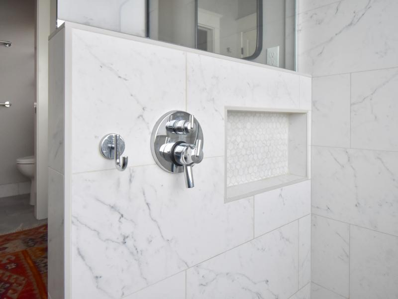 Large format subway tile shower wall with niche and controls