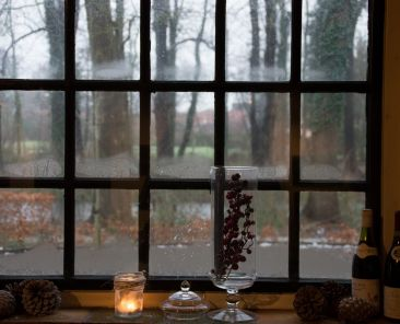 Window with pinecones and candle and wine