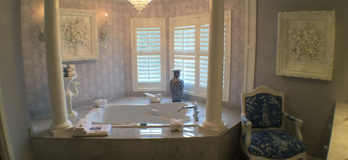 Drop in bathtub with marble tile surround and pillars