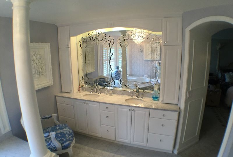 Remodeled bathroom vanity with white panels and quartz countertop