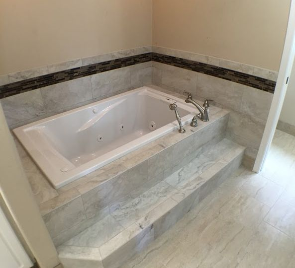 Drop-in tub surrounded by marble tile